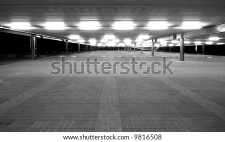 an empty spacious parking lot by night in black and white #9816508