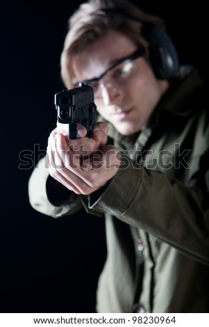 Man aiming a gun with protective gear #98230964
