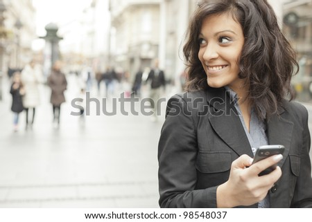 Young Woman with smartphone walking on street, downtown. In background is blured street #98548037