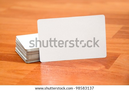 Stack of business cards with rounded corners on wood background