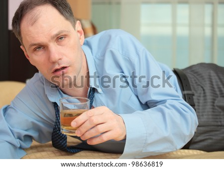 Drunk businessman on a bed in hotel room holding a glass of whiskey #98636819