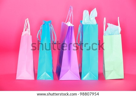 Shopping bags on pink background. Many colorful shopping paper bags standing on pink floor.