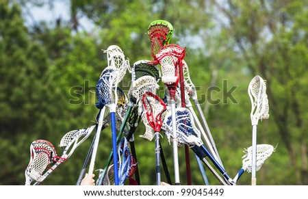 Colorful lacrosse sticks raised in the air