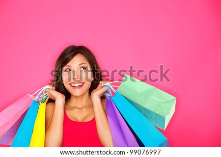 Shopping woman holding shopping bags looking up to the side on pink background at copy space. Beautiful young mixed race Caucasian / Chinese Asian shopper smiling happy. #99076997