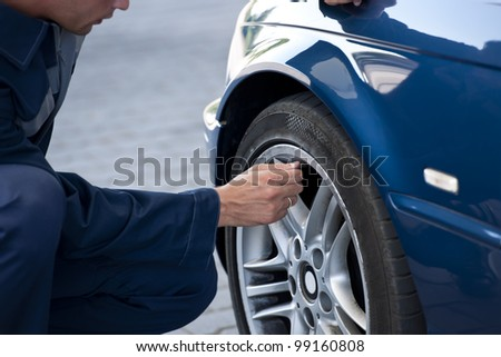 Auto mechanic/Service station worker  reviews necessary repairs or inflating #99160808