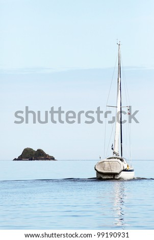 Sailing boat and small island on the sound of Raasay, Scotland #99190931