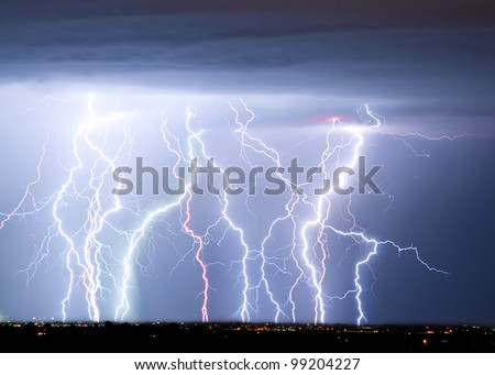 Massive colorful cloud to ground lightning bolts hitting the horizon of city lights.