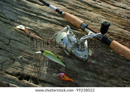 Rod, reel and wobblers on the wood #99238022