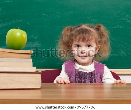 Cheerful smiling child with a book and apples against blackboard  in a class . Looking at camera. School concept