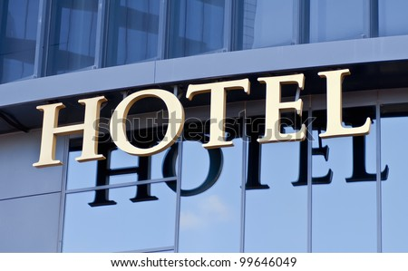 A hotel sign reflected in the glass of the building