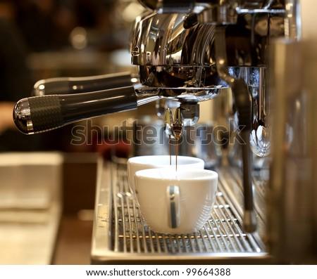 prepares espresso in his coffee shop; close-up Royalty-Free Stock Photo #99664388