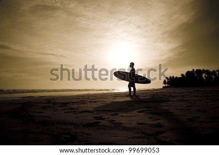 Sunset on the beach with surfer watching waves.