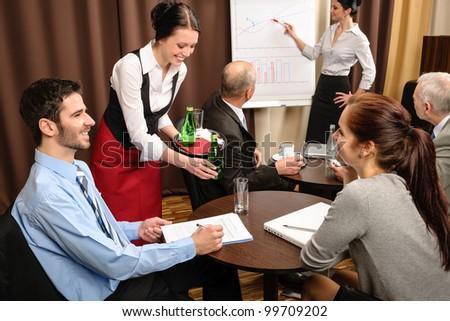 Waitress serving people at business meeting flip-chart presentation #99709202