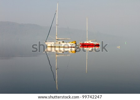 Colourful boats on a foggy Lake Windermere, Lake District #99742247