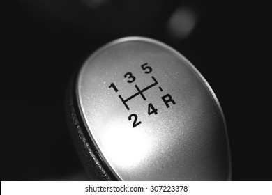 An image of a 5-speed manual drive gear stick. Image has a strong black and white effect applied to create some dramatic angle to the image.