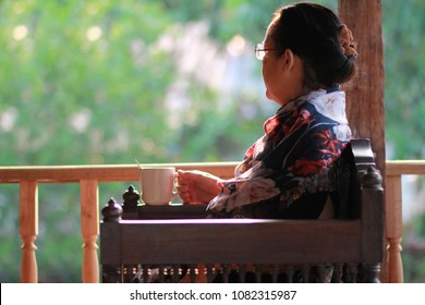 Image of 60s or 70s  Asian elderly woman lonely with cold coffee in the morning.She looking outside or flew away ,rim light or warm Mornings light upon her body.Sad elderly concept.