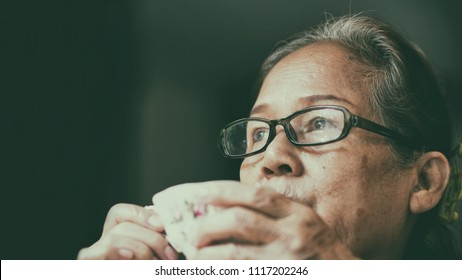 Image of 60s or 70s  Asian elderly drinking tea.Old woman wearing eye glasses,lonely with cold cup.She looking outside or flew away ,Vintage film color tone.Sad elderly concept.
