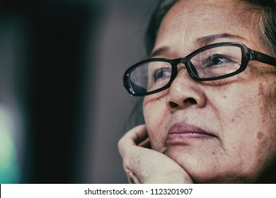 Image of 60s or 70s  Asian elderly woman wearing eyeglasses rest her chin on her hands .She looking outside or flew away.Sad elderly concept.