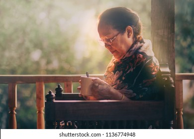 Image of 60s or 70s  Asian elderly woman lonely with a cup of coffee.She looking at the cup and flew away ,rim light or warm Mornings light upon her body.Sad elderly concept.