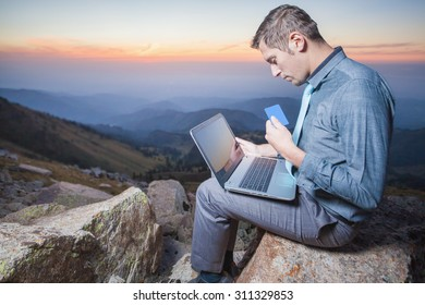 Image of achieve and successful businessman on the top of mountain, using a laptop for online payment by plastic card through the Internet banking