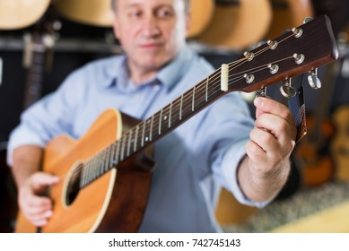Image of acoustic guitar close-up in time tuning on it in music store