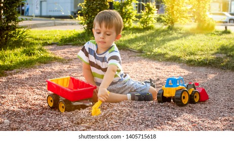 Image of adorable 3 years old toddler boy playing with sand and you truck and trailer in park. Child digging and building in sandpit