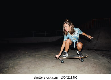 Image of adorable caucasian girl in streetwear smiling and riding skateboard at night outdoors