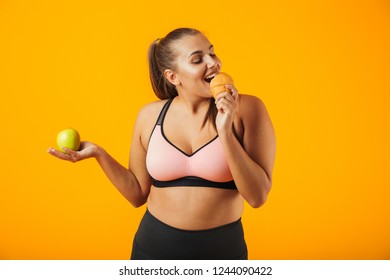 Image of adorable chubby woman in tracksuit holding apple and eating croissant isolated over yellow background