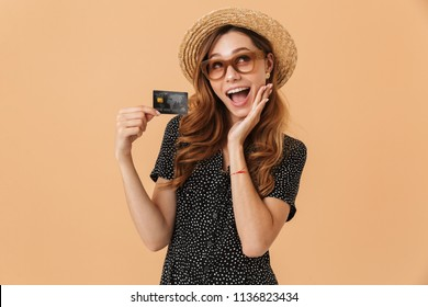 Image of adorable excited woman wearing straw hat and sunglasses rejoicing and holding credit card isolated over beige background