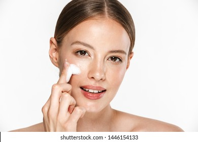 Image of adorable half-naked woman washing her face with foaming facial cleanser isolated over beige background