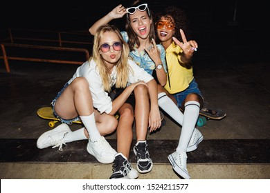 Image of adorable multinational girls in streetwear smiling and sitting on skateboards at night party outdoors