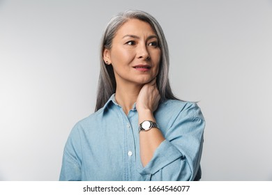 Image of adult mature woman with long white hair wearing shirt looking aside at empty space isolated over gray background