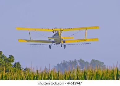 Image of aerial crop duster spraying corn field in rural Iowa.