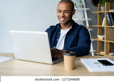 Image of african american businessman working on his laptop. Handsome young man at his desk.