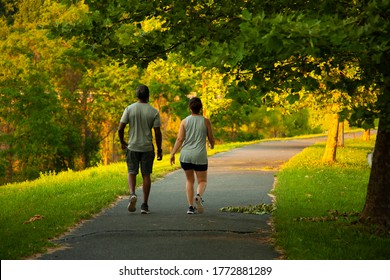 Image of an African American man and a caucasian woman walking on a hiking trail. The couple wears matching vests, shirts, shorts and sneakers. These two people walk peacefully on a sunny day
