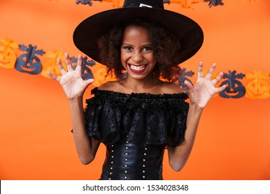 Image of african american witch girl in black halloween costume looking at camera and scratching isolated over orange pumpkin wall