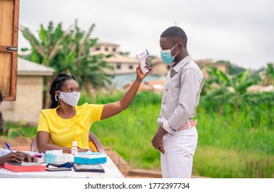 image of African health official checking temperature during covid-19 season-black church usher pointing thermometer gun on a church member before entry with Bible and records book on table