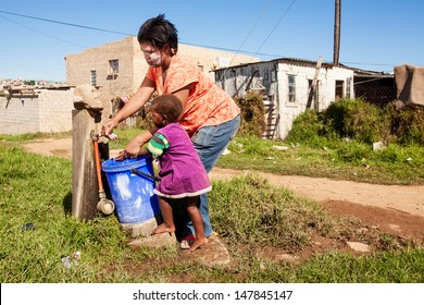image of an african mother cleaning her daughters hands under running water in the township