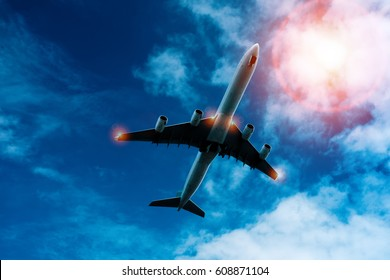 image of airplane flying over blue sky and the sun.