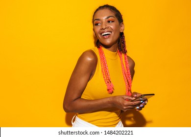Image of alluring african american woman with afro braids smiling and holding smartphone isolated over yellow background