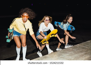 Image of alluring multinational girls in streetwear smiling and riding skateboards at night outdoors