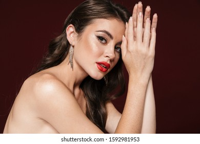 Image of alluring shirtless woman wearing earrings looking at camera isolated over burgundy background