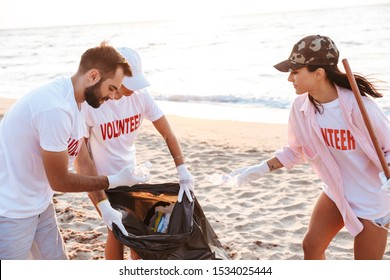 Image of altruistic eco volunteers cleaning beach from plastic with trash bags at seashore