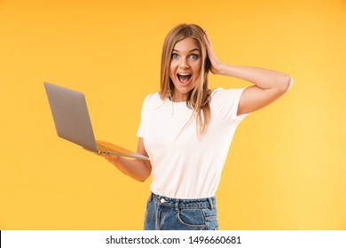 Image of amazed blond woman wearing casual t-shirt expressing wonder while using laptop computer isolated over yellow background in studio