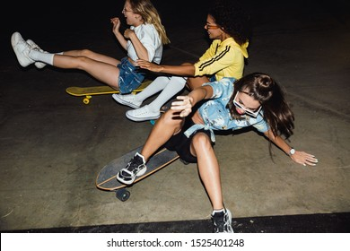 Image of amazed multinational girls in streetwear smiling and riding on skateboards at night party outdoors