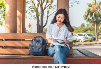 Image of an amazing beautiful woman sitting on a bench in park reading book.