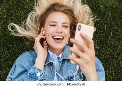 Image of amazing excited happy young woman posing outdoors in park using mobile phone listening music with earphones lies on grass.