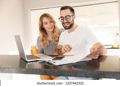 a448864c91 Image of amazing happy young loving couple sitting at the kitchen using  laptop computer.