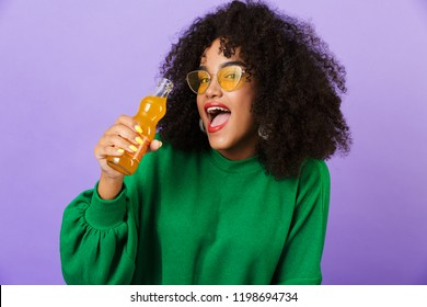 Image of amazing pretty african woman isolated over violet background drinking soda.