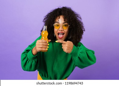 Image of amazing pretty african woman isolated over violet background pointing drinking soda.
